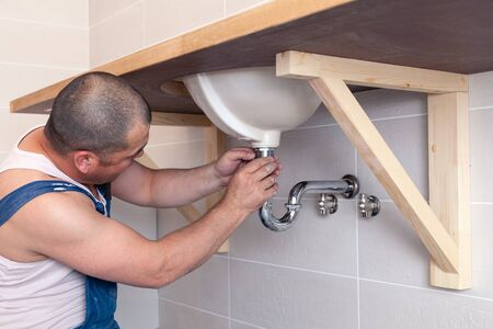 Closeup male plumber worker in blue denim uniform, overalls, fixing sink in bathroom with tile wall. Professional plumbing repair service, installation water pipes, man mounted sewer drain Imagens