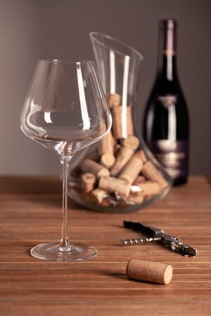 Crystal shiny red wine glasses, bottle, corkscrew, opener, sommelier knife, transparent decanter with corks on wooden table. Closeup, vertical, selective focus, side view. Concept wine magazine photo Banque d'images - 137892108