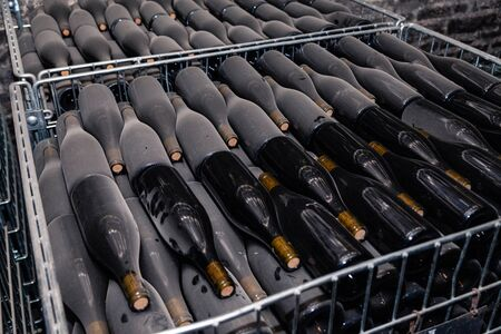 Ancient wine bottles resting, aging, dusting in underground cellar in rows. Concept winery vault with rare wines, exclusive collection. Stacks of wine bottles laying flat in racks in old cave Banque d'images - 139381381