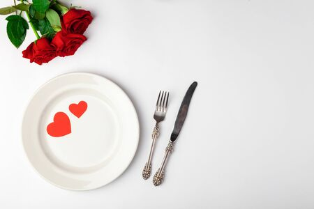 Valentines day dinner with festive table setting, red roses, tape, hearts, ceramic plate, vintage silverware on white background. Top view, space for text, copy space, birthday greeting, anniversary