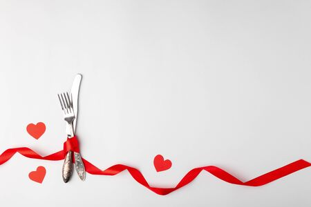 Anniversary, birthsday festive romantic table setting on white background. Silverware, vintage fork, knife with red ribbon, paper hearts. Place for text, copyspace, topview