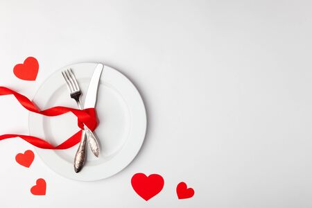 Romantic table setting on white background. Valentines day card template. Red ribbon, plate, silverware, vintage fork, hearts, knife. Concept anniversary, birthday, place for text, copyspace topview Banco de Imagens