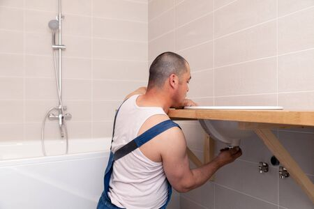 Closeup male plumber worker in blue denim uniform, overalls, fixing sink in bathroom with tile wall. Professional plumbing repair service, installation of water pipes, man mounted sewer drain Imagens