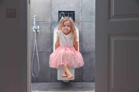Cute little girl in white pink dress sitting on toilet with toilet paper on background of walls with gray tiles, view from open door. Stock Photo