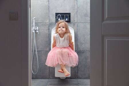 Cute little girl in white pink dress sitting on toilet with toilet paper on background of walls with gray tiles, view from open door.