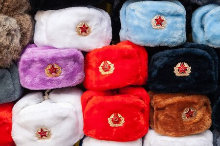Earflaps fur caps with red stars in souvenir shop in Moscow street. Winter hats, soviet and russian military uniform, travelling to Russia, tourist gifts. Foto de archivo