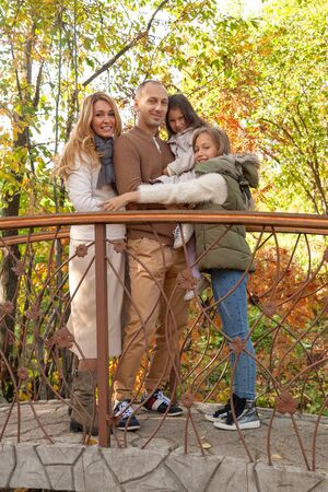 Happy family hugs in autumn forest park