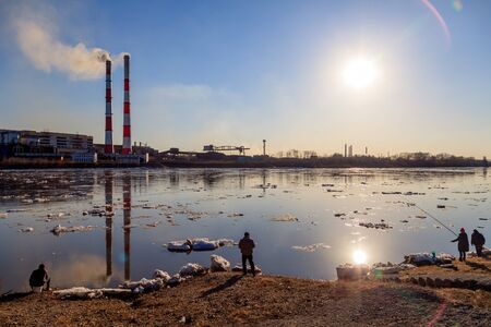 People catch fish on river coast against coal plant, smoke of pipes polluted city atmosphere. Concept of oil, gas processing, emissions into water resources, oncological diseases, cancer