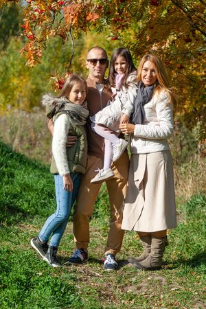 Happy family, daughthers in autumn forest park 스톡 콘텐츠