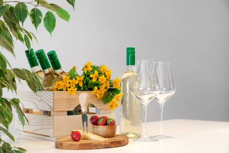 Wine glasses, bottles of white wine with green cap, bright yellow flowers in wooden party box standing on table, fresh red strawberry, cheese on white background, copy space, mockup, horizontal Foto de archivo