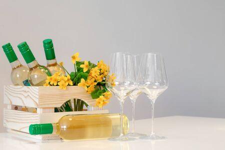 Wine glasses, bottles, yellow flowers in wooden box
