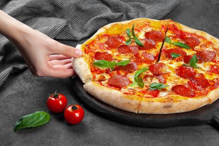 Female hand take slice of pepperoni pizza with basil Banque d'images