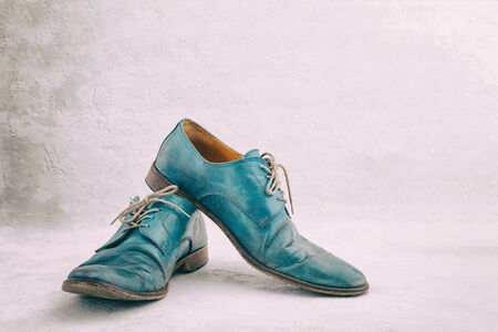 Pair of old leather blue discarded boots with laces