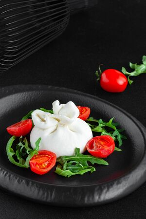 Portion of fresh white goat cheese with burrata with arugula and cherry tomatoes Foto de archivo
