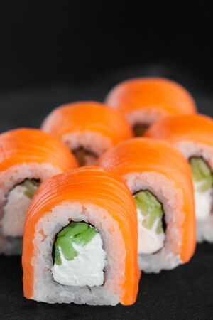 Portion of fresh philadelphia sushi roll on black background