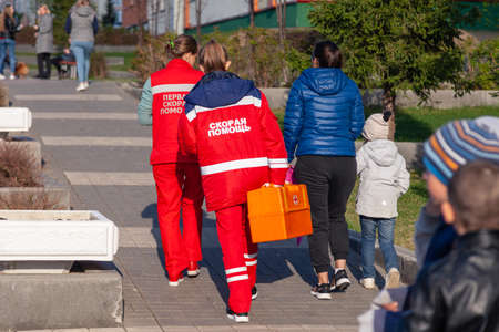 Russia Kemerovo 2019-05-21 Ambulance team of a woman in a red uniform with an orange medicine case is walking down the street in the park in the fall. Back view