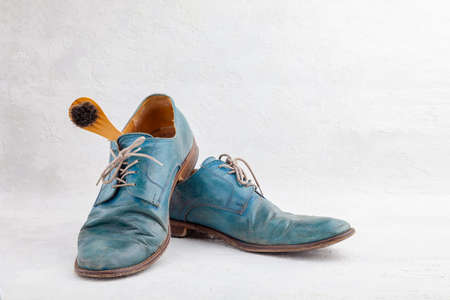 Pair of old leather blue boots with laces with shoe brush