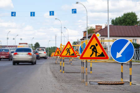Asphalt road repairs, yellow warning triangle signs about road works and bypass directions Archivio Fotografico