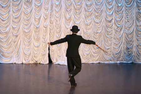 Tap dance with a cane in a black hat. Dance step. A man is dancing on stage.