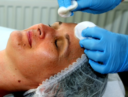 Girl on the cosmetic procedure. Face cleaning. Fractional rejuvenation. Botox. Laser resurfacing