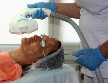 Girl on the cosmetic procedure. Face cleaning. Fractional rejuvenation.