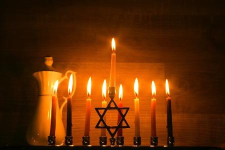 Hanukkah is a Jewish holiday. Burning Chanukah candlestick with candles. jug of oil. Chanukiah Menorah.