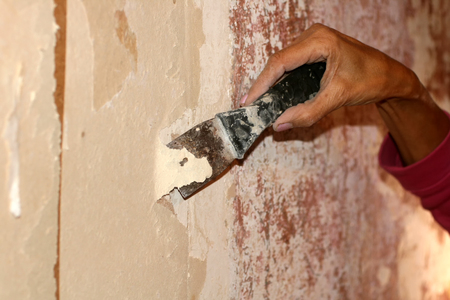 Preparing walls for wallpaper with a spatula. Repair in the apartment.