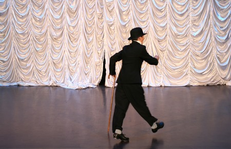 Tap dance with a cane in a black hat. Dance step. A man is dancing on stage 版權商用圖片