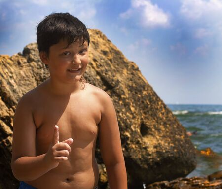 Boy emotion warning index finger up. Child on the background of the sea and stones.
