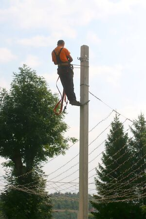 Installation of switching and connecting overhead electrical lines on a pole. An electrician is working on a pole.