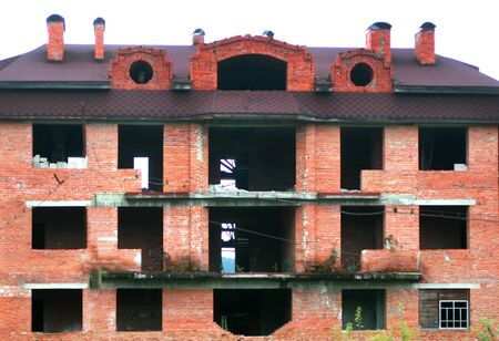 Large unfinished house of red brick. Four-story house box. Banco de Imagens