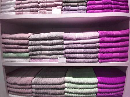A pile of multi-colored terry towels on a shelf. Zdjęcie Seryjne