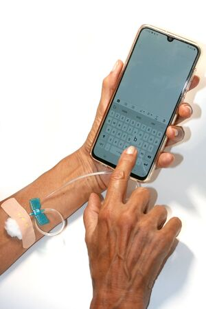 Smartphone dropping medicine. A dropper in a man hand.