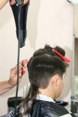 Haircut of a boy at the hairdresser. Trimer