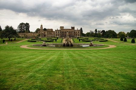 Witley Court garden with fountain. Dramatic sky. Green grass. Editorial