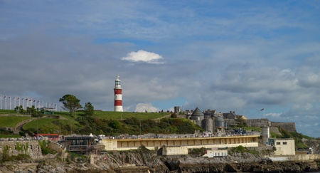 Plymouth in England with lighthouse at background. Dramatic cloudy sky.