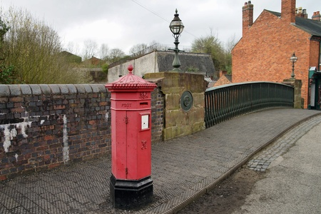 British red postbox for collection of letters on the bridge. Stock fotó