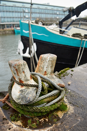 Ship docked to an old Rusty Iron Mooring in ocean harbour. 스톡 콘텐츠