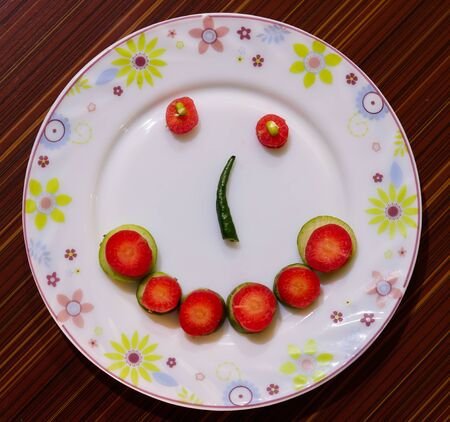 SMILING HEALTHY SALAD IN SERVING PLATE INVITES YOU FOR HEALTHY LIFE STYLE Banque d'images