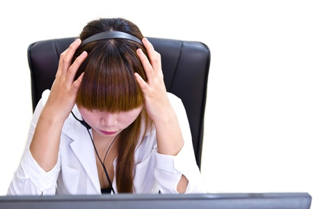 Young tired business woman with headache sitting at computer in workplace holding head photo