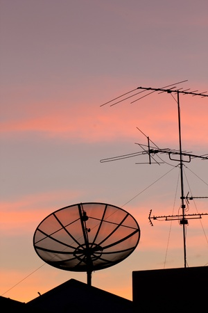 Black satellite dish in sunset sky photo