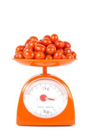 many fresh small tomato lying on weight scale Stockfoto
