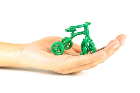 A small green toy bicycle in hand