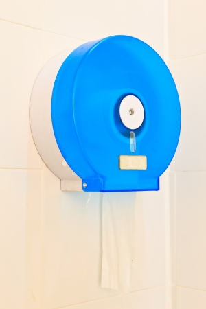 Modern tissue hanging on the wall. Toilet modern paper on white tiles photo
