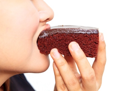 Young beautiful woman is eating a brownie photo