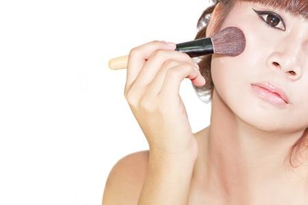 Young beautiful asian woman applying powder on cheek with brush Stockfoto