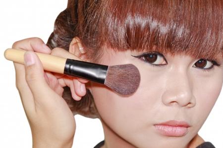 Young beautiful asian woman applying powder on cheek with brush photo