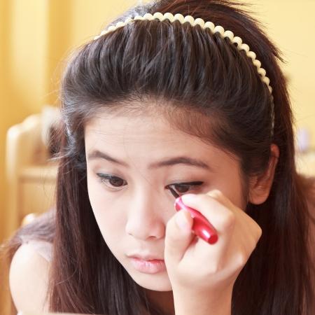 Young beautiful girl applying eyeliner