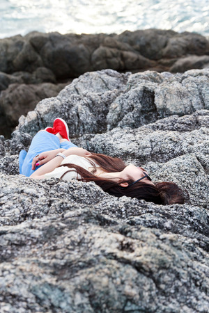 Girl sleeping at reef on background of the bay, Puket in Thailand photo