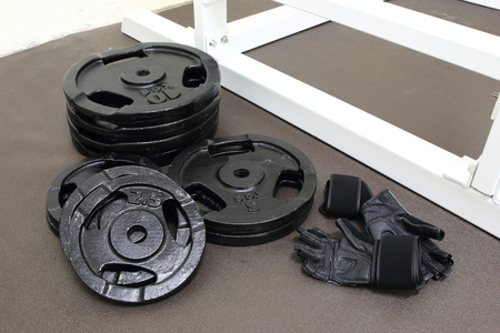 weightlifting gloves: Barbells weight plate and gloves in gym room Stock Photo
